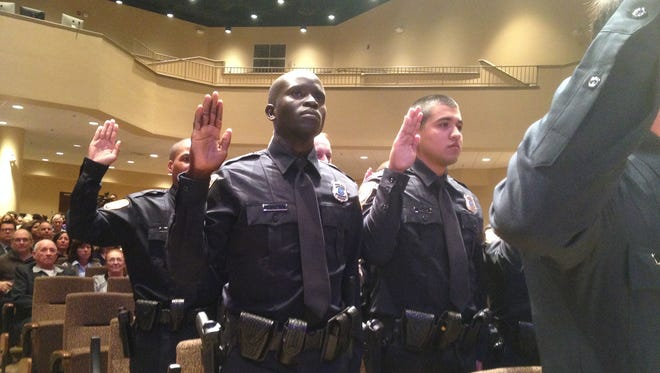 John Liom (left), who came to Memphis as a refugee from Sudan, is sworn in early in 2017 as a Memphis police officer. He qualified under old standards that required recruits to have college courses. He said at the time that he was short of the required college credits and was turned down more than once before he qualified. The department has since loosened the standards.