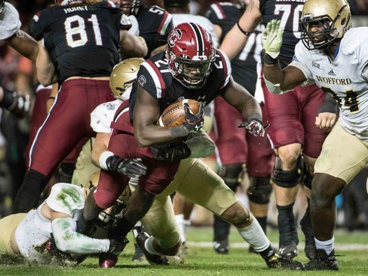 South Carolina running back Ty'Son Williams (27) runs the ball against Wofford safety Mason Alstatt, left and Deon Priester (94) during the second half of an NCAA college football game on Saturday, Nov. 18, 2017 in Columbia, S.C. South Carolina defeated Wofford 31-10. (AP Photo/Sean Rayford)