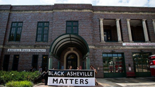 """Community members and organizers from Showing Up for Racial Justice hold up a Black Lives Matter sign outside the Asheville Police Department Thursday morning July 21, 2016. Organizers planned to sit inside the station's lobby until the police meet their demands - accountability in the killing of Jerry """"Jai"""" Williams and an end to police violence towards people of color - or until they were arrested."""