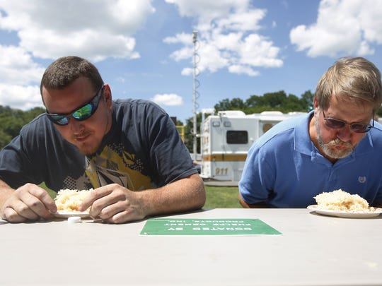 Patrick Middlebrook of Phelps and John Daly of Virginia eat face first a plate of sauerkraut during the sauerkraut eating contest during the Phelps Sauerkraut Festival on  August 2, 2015.   Middlebrook won.