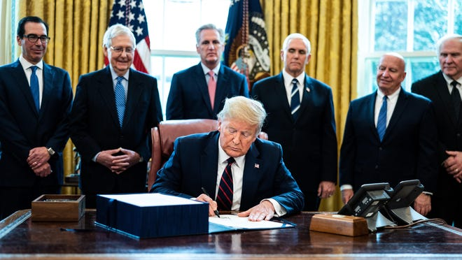 U.S. President Donald Trump signs H.R. 748, the CARES Act in the Oval Office.