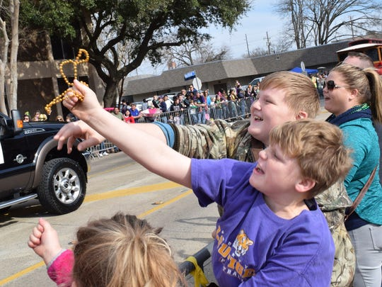 Trenton Strong (front) and his cousin Lane Ashmore grab for a string of beads thrown during the Children's Mardi Gras Parade held Saturday in downtown Alexandria.