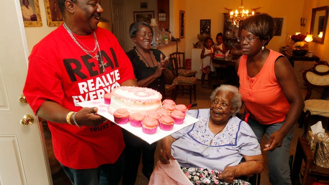 """Terrance Jackson, left, Doris Ware, second from left, and Beverly Booker, right, sing the """"Happy Birthday Song"""" to Bernice Williams, seated, as she celebrates her 103rd birthday July 25, 2015, in the Mill City neighborhood of Dallas."""