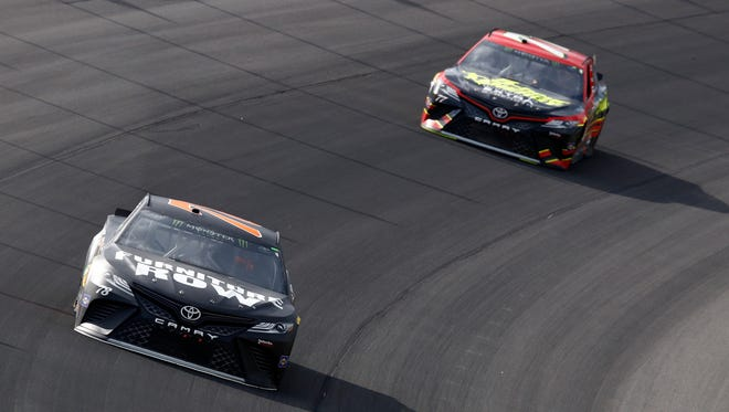 Martin Truex Jr., left, leads Furniture Row Racing teammate Erik Jones, right, during Sunday's race at Michigan International Speedway.