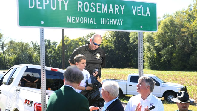 Jayden Wilkes helped unveil the sign for the Deputy Rosemary Vela Memorial Highway, named after his mother, Friday afternoon.