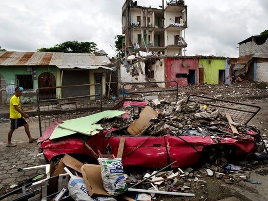 A man walks amid de debris of a destroyed car and buildings,