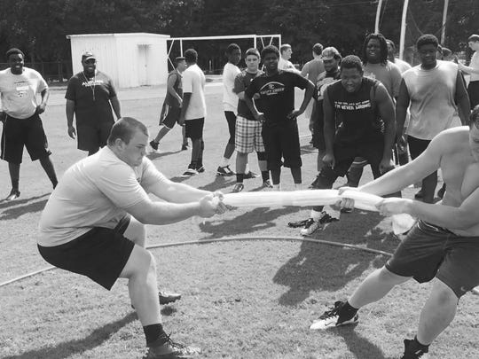 "Lincoln Trojans offensive linemen Tom Moss (left) and Casey Warming square off in a tug-of-war battle during summer workouts last week, on a day dubbed ""Competition Thursday."""