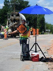 Trey Swarthout of Dilbeck Excavation directs traffic from under an umbrella Thursday on AR Highway 201 south in Mountain Home. With temperatures soaring experts say it's a good idea to seek shade, if possible, when working outside.