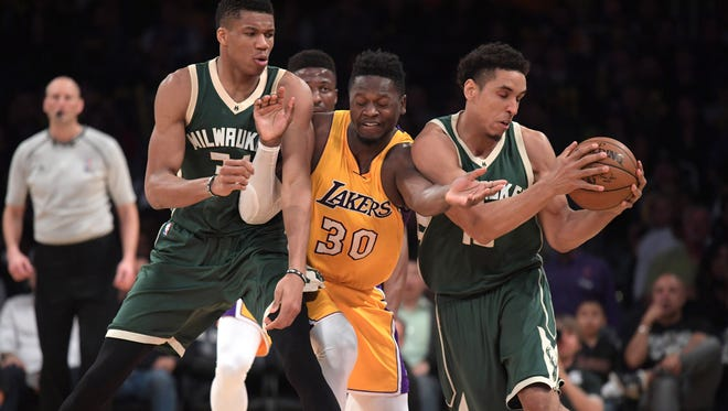 Lakers forward Julius Randle battles for the ball with Milwaukee Bucks forward Giannis Antetokounmpo (left) and guard Malcolm Brogdon.