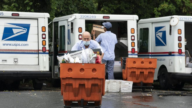 Letter carriers load mail trucks at a U.S. Postal Service facility in McLean, Va. Many states have switched to voting by mail.