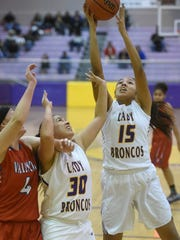 Kirtland Central senior guard Orquidea Reyes, No. 30, watches as teammate Megan Silversmith shoots after a battle for the rebound during Sturday's game against Valencia at Bronco Arena in Kirtland.
