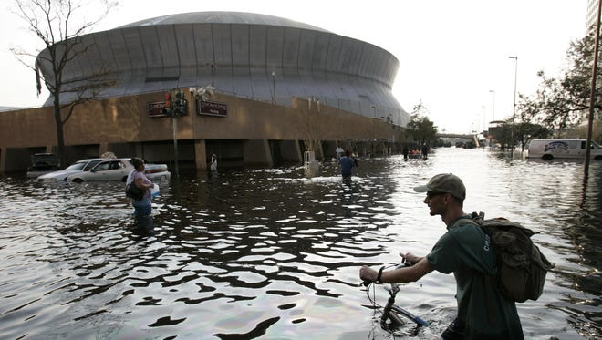 This Aug, 31, 2005, file photo shows a man pushing his bicycle through flood waters near the Superdome in  New Orleans after Hurricane Katrina left much of the city under water. A new but controversial study asks if an end is coming to the busy Atlantic hurricane seasons of recent decades. The Atlantic looks like it is entering in to a new quieter cycle of storm activity, like in the 1970s and 1980s, two prominent hurricane researchers wrote Monday in the journal Nature Geoscience.