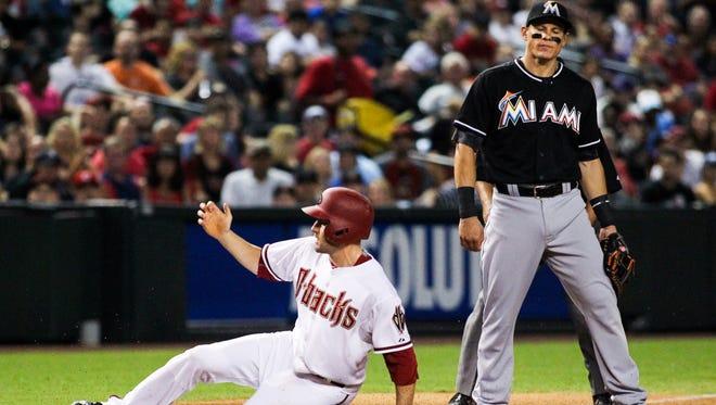 Arizona Diamondbacks center fielder A.J. Pollock  steals third base as Miami Marlins third baseman Derek Dietrich stands by in the sixth inning at Chase Field in Phoenix, AZ, on Tuesday, July 21, 2015.