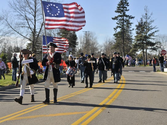 Marchers in the Veterans Day Parade wear the uniforms