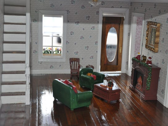 The restored dollhouse features Christmas-themed décor.