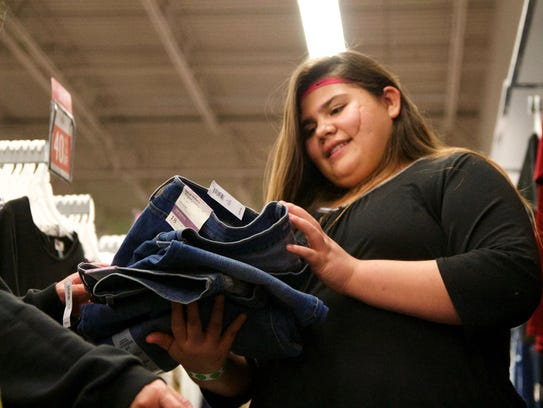 Alicia Chavez, 13, sifts through a pile of jeans during