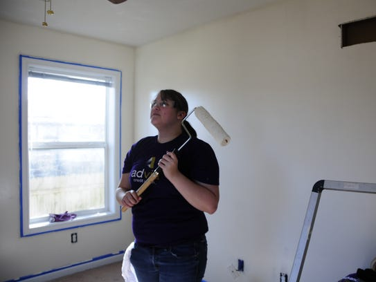 Volunteer Ashley Eagle sizes up an interior wall to