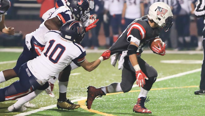San Joaquin Memorial's Andrew Defendis (10) tries to pull down Tulare Western's David Alcantar (C)  (43) during the Central Section Division II Championship high school football game Bob Mathias Statium on Dec 1, 2017.