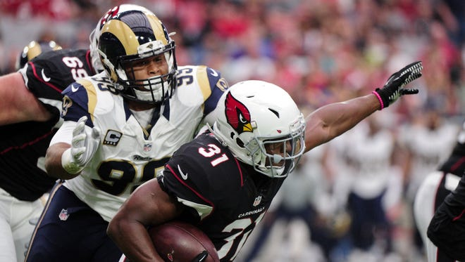 Arizona Cardinals running back David Johnson (31) carries the ball as Los Angeles Rams defensive tackle Aaron Donald (99) defends during the first half at University of Phoenix Stadium, Oct. 2, 2016.