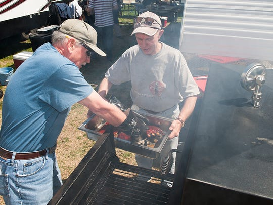 Mick Maguire and Tim Moran, both of New Castle, with Bad Dog BBQ prepare their ribs for judging at the BBQ competition.