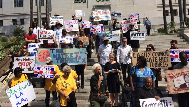 """A small group of protesters carrying signs that said """"Water is a human right"""" and """"Stop the water tunnel tax"""" gather at Los Angeles City Hall on Monday, Sept. 18, 2017 to urge Mayor Eric Garcetti and other local officials to come out against the planned Delta Tunnels."""