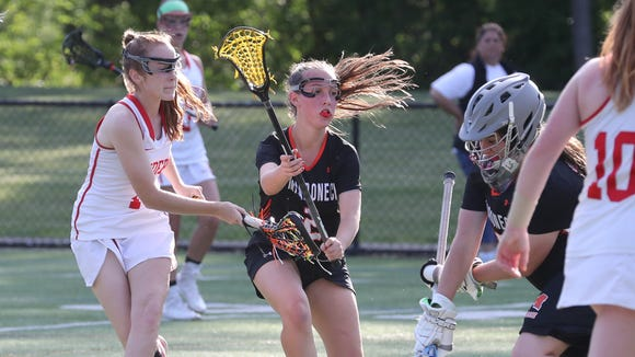 North Rockland's Phoebe Malarkey scores past Mamaroneck defender Anna Giarraputo and goalie Chloe Stafford during the Section 1 Class A girls lacrosse championship at the Torne Valley Athletic Center May 23, 2018.