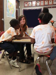Leandra Morgan works with two second-grade students in her classroom, which has adopted Auburn University, at East Elementary School in Humboldt.