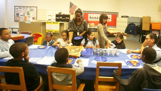 Michelle Peguese, left, works for the Department of Human Services as a success coach for the Pathways to Potential program and Jessica Schulte is a prevention specialist at WHRC Elementary School in Pontiac. They are saluting students who have perfect attendance with a pizza, cupcake and certificate presentation party. The students are from left back: Anthony Rogers, 7, Kur'an Dalton, 9, both second graders, Kenneth Harris, 11, a sixth grader, Shardonnae Wright, 7, Savonna James, 7, Arianna Paloma-Moreno, 8, Gioanna Garcia, 7, all second graders, Sara Reyes, 11 and Cedric Love, 10, both fifth graders.