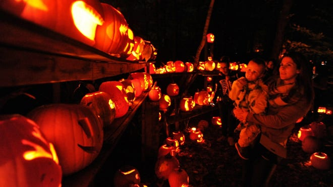 Children and adults check out the hundreds of illuminated carved pumpkins during the 17th annual Night of a Thousand Faces at the New England Wildlife Center in Weymouth on Saturday, Oct. 26, 2019. Tom Gorman/For The Patriot Ledger