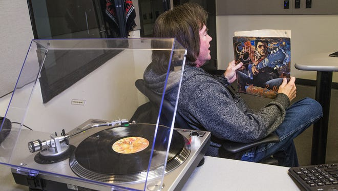 KSLX radio personality Russ Egan looks at a Gerry Rafferty album from 1978 during his show on KSLX in Phoenix.