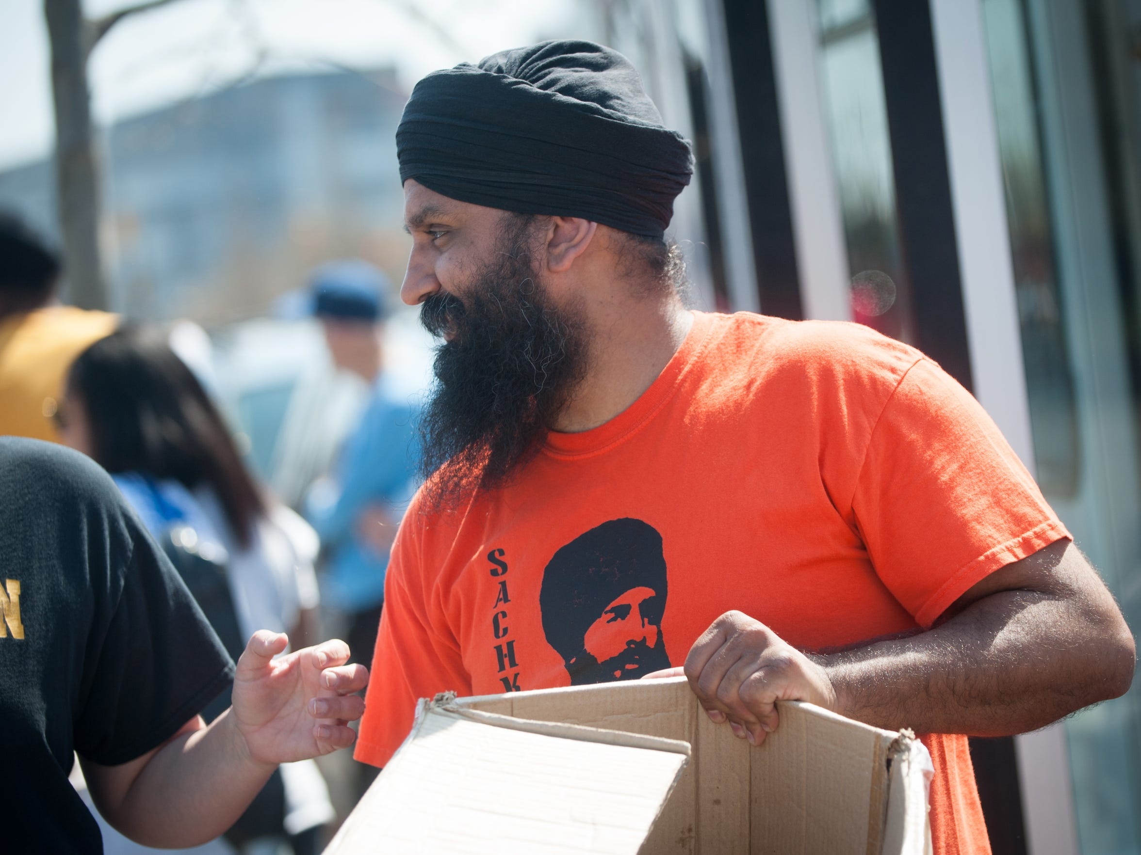 Tony Rahil chats with volunteers as they distribute food to passersby on Martin Luther King Blvd. in Camden, N.J. on Saturday, April 14, 2018. Volunteers from the Sikh Coalition come from throughout Pennsylvania and New Jersey to distribute food and clothing at this location every month.