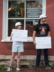 Claire, 12, and Ian Macdonald protest in front of The Red Hen restaurant on June 26, 2018.