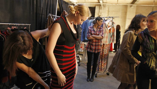 Fashion designer Andrea Geer, left, helps model Cady Stoever, Rochester, put on one of her creations backstage at the Fashion Week opening fashion show at the Factory on Russell Street in Rochester Thursday, Oct. 17, 2013.
