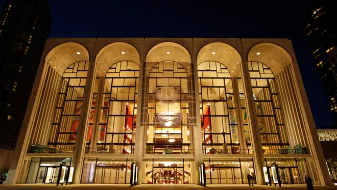 The Metropolitan Opera House is illuminated at dusk in New York's Lincoln Center.