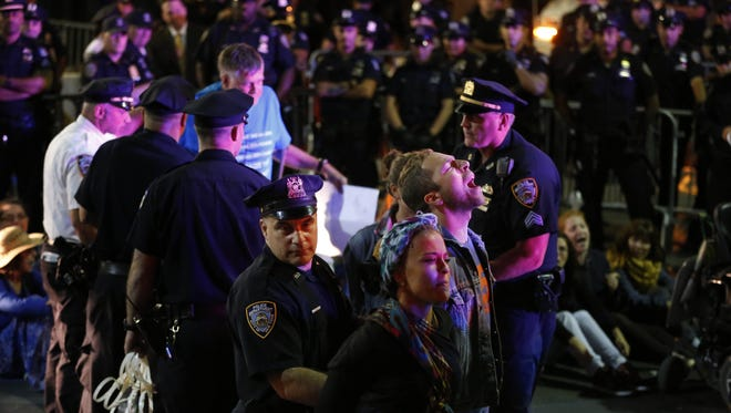 Protesters chant as they are arrested at the intersection of Wall St. and Broad St. in New York, Monday, Sept. 22, 2014. The protesters, many who were affiliated with Occupy Wall Street, were trying to draw attention to the connection between capitalism and environmental destruction. Over a hundred protesters that would not move from the intersection were taken into custody. (AP Photo/Seth Wenig)