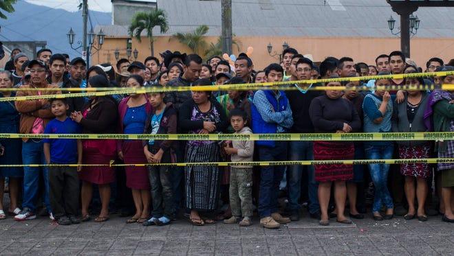 Neighbors stand outside a temporary morgue in Alotenango, Guatemala, on June 3, 2018.