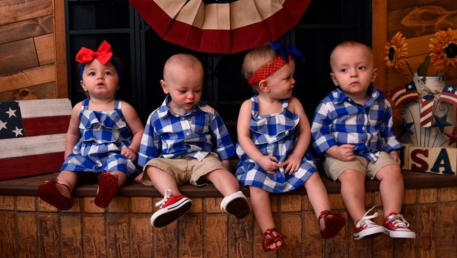 Aspen (left), Abbott, Auree, and Anson Anders sit in front of the fireplace at their home in Tuscola on Tuesday. The quadruplets recently celebrated their first birthday.