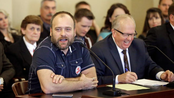 """Brady Williams, left, testifies while Republican Rep. Mike Noel, right, of Kanab, laughs during a hearing Friday, Feb. 19, 2016, in Salt Lake City. Utah polygamists came to the state Capitol on Friday to tell lawmakers that a proposal to revive a ban on living with multiple spiritual wives would wrongly keep families like theirs in the shadows. """"It's unconstitutional to say I can't live and love and cohabitate with whoever I choose, so why are we revisiting this?"""" said Williams, who has five wives. """"Let's just leave it alone."""""""