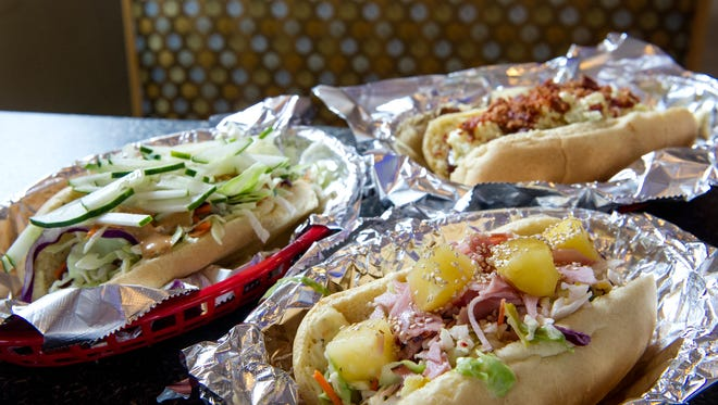 Hot dog creations are displayed including the Thai (from left), the Hawaiian and the Curious at Curious Dog Hotdogs and Sandwiches on Jackson Avenue in Knoxville Saturday, June 27, 2015.  JESSICA TEZAK/NEWS SENTINEL)