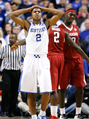 Kentucky Wildcats guard Aaron Harrison (2) reacts against Arkansas Razorbacks forward Alandise Harris (2) and guard Rashad Madden (0) in the second half at Rupp Arena. Arkansas defeated Kentucky 71-67.