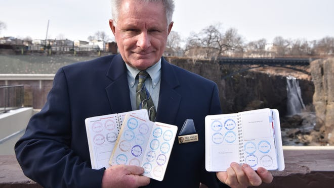 Dr. Paul Kovalski of Monmouth County, displays his park books with stamps from all the park he visited, along with Paterson's Great Falls on Friday, December 23.