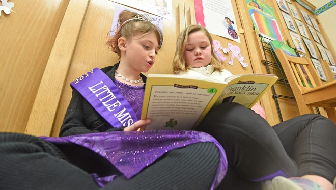 Second graders Valarie Duffey reads with Addison Williams on Thursday morning at Central Elelmentary in Lexington. Duffey is conducting a drive to collect fabric and elastic so that she can sew caps for sick children in the Golisano Children's Hospital in Rochester, New York.