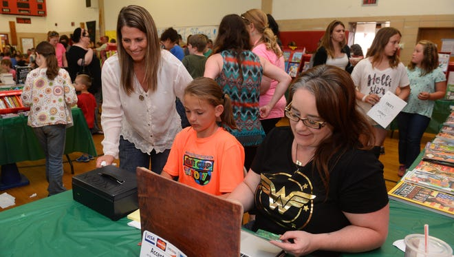 Julie Pachek, left, a PTA volunteer at Lincoln Elementary, looks on while her daughter Isabella, age 11, and Laura Wright, a PTA board member, ring up customers at the Lincoln Elementary Ice Cream Social and Book Fair on May 30th.