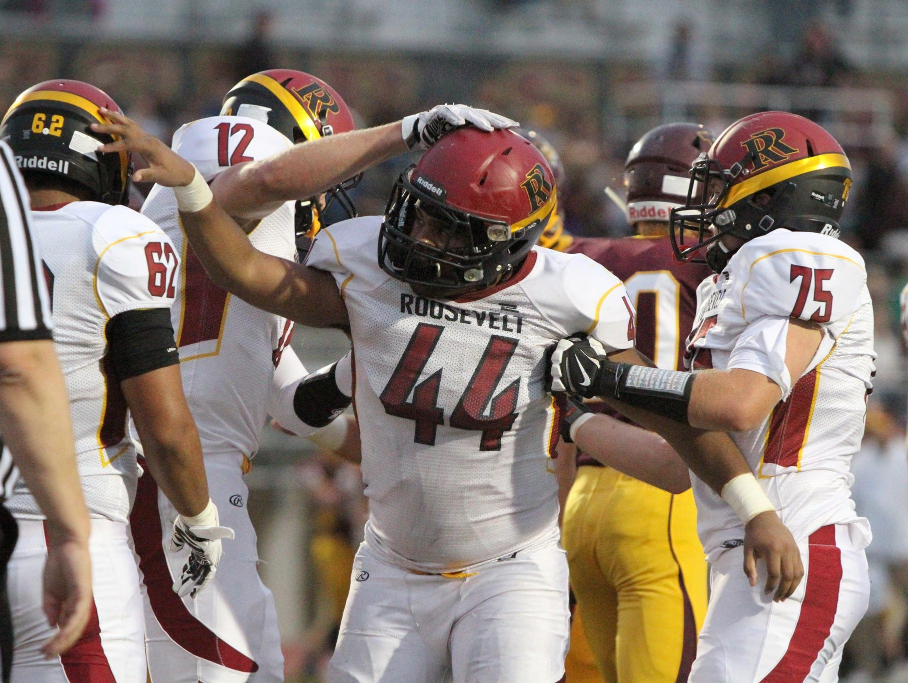 Piercen Evans celebrates with his teammates after scoring Roosevelt's second touchdown of the first quarter on a one-yard run.
