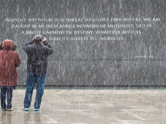 Visitors to the Martin Luther King, Jr. Memorial in Washington stop to photograph the quotes etched into the memorial's back wall while it snows in the Nation's Capital, Sunday, Jan. 17, 2016. The civil rights leader's birthday is celebrated as a federal holiday Monday. (AP Photo/J. David Ake)