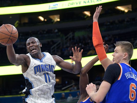 Orlando Magic center Bismack Biyombo (11) is fouled by New York Knicks guard Justin Holiday, center, while going up for a shot as Knicks forward Kristaps Porzingis (6) watches during the first half of an NBA basketball game in Orlando, Fla., Monday, March 6, 2017. (AP Photo/Phelan M. Ebenhack)