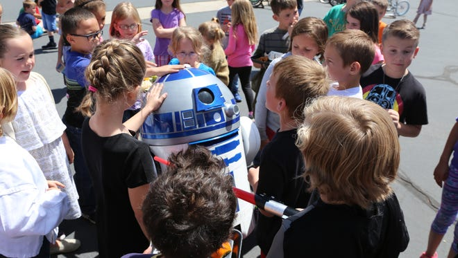 """R2D2 visits """"younglings"""" and """"padawan"""" learners at Hurricane Elementary  School during Star Wars Day activities at lunch recess Wednesday, May 4, 2016, in Hurricane, Utah."""