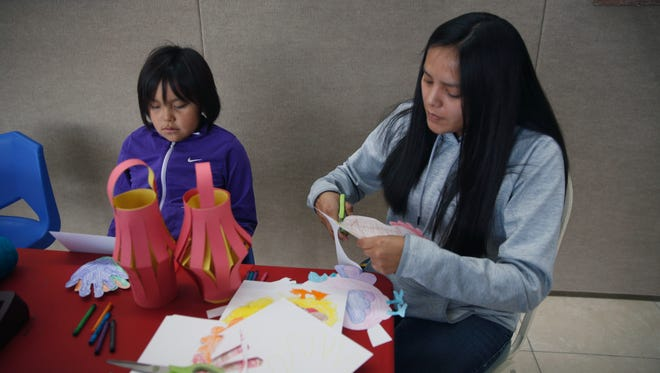 Sofia Nez, left, and her mother Danielle Greyeyes work on cutting out a rooster drawing during a Chinese New Year celebration Saturday at the Farmington Museum at Gateway Park.