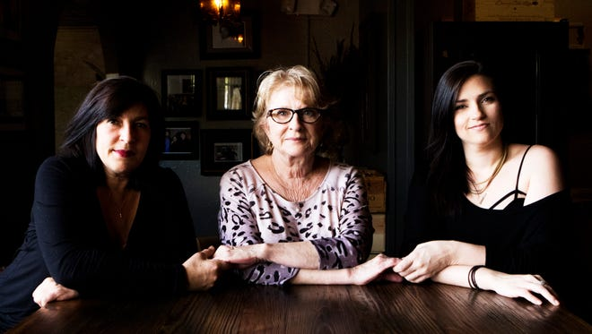 Rachel (Genusa) Dickey, left, and Ashley Genusa, right, holds hands with Cherry Genusa at the family's restaurant in Monroe on Tuesday, February 7, 2017. They, along with Ann (Genusa) Williamson, not pictured, will take over the restaurant, which has been in business since the 1940s. Dickey handles the food and wine. Ashley Genusa manages the books.