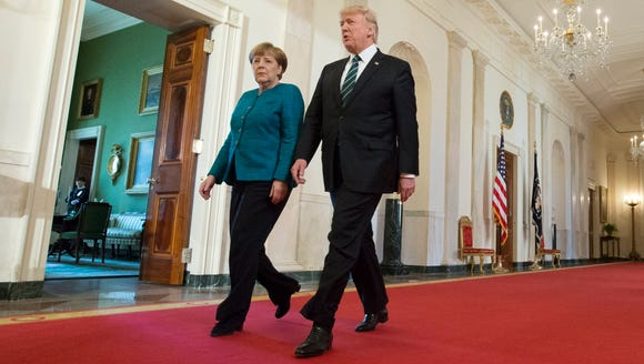 Trump and German Chancellor Angela Merkel walk down
